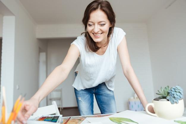 Felice attraente giovane pittrice che lavora in uno studio d'arte