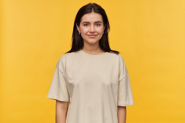 Felice giovane donna attraente con i capelli scuri in maglietta bianca in piedi sorridente sul muro giallo