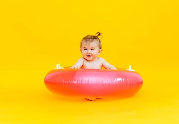 Bambino felice di 10 mesi con un cerchio di nuoto seduto su uno sfondo giallo, foto in studio del bambino in un cerchio di nuoto
