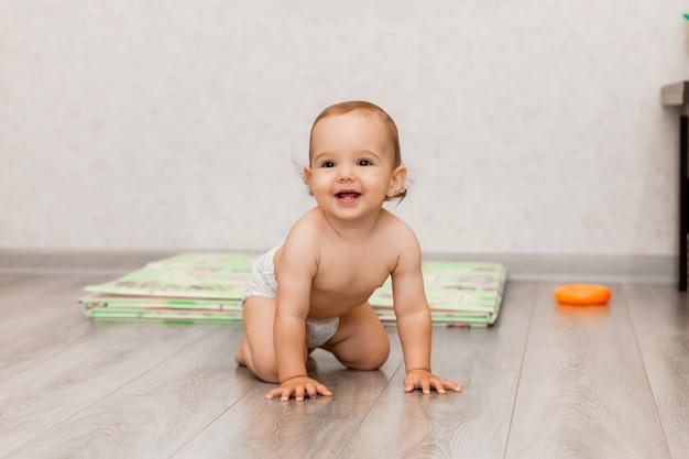 Il bambino felice di 11 mesi striscia sul pavimento e ride. il bambino è seduto sul pavimento.