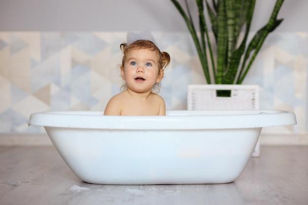Il bambino felice fa il bagno in bagno
