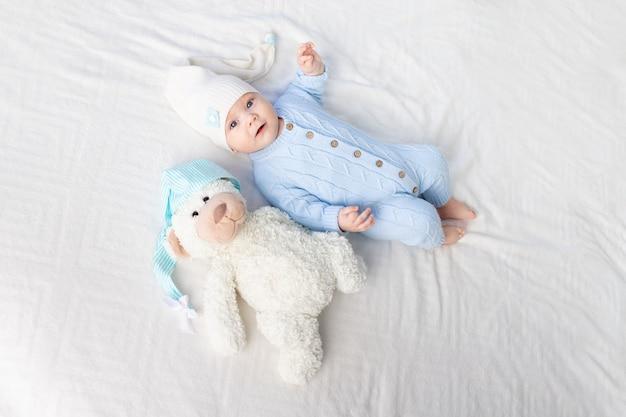 Bambino felice sul letto in un cappuccio. tessili e biancheria da letto per bambini. neonato con un orsetto giocattolo