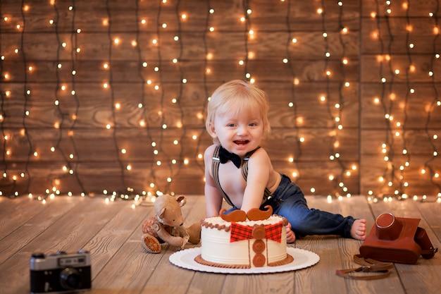 Bambino felice di mangiare la prima torta con le mani