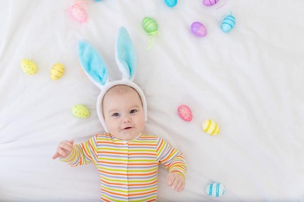 Neonato felice con le orecchie di coniglio sulla sua testa sdraiato sul letto con le uova di pasqua, piccolo bambino sorridente divertente sveglio.