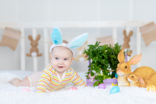 Neonato felice con le orecchie di coniglio sulla sua testa che si trova con un coniglio sul letto con le uova di pasqua, piccolo bambino sorridente divertente sveglio.