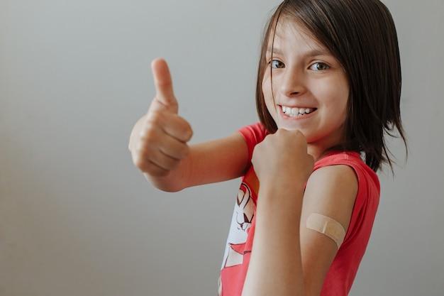 Bambina felice dopo la vaccinazione con un cerotto sulla spalla