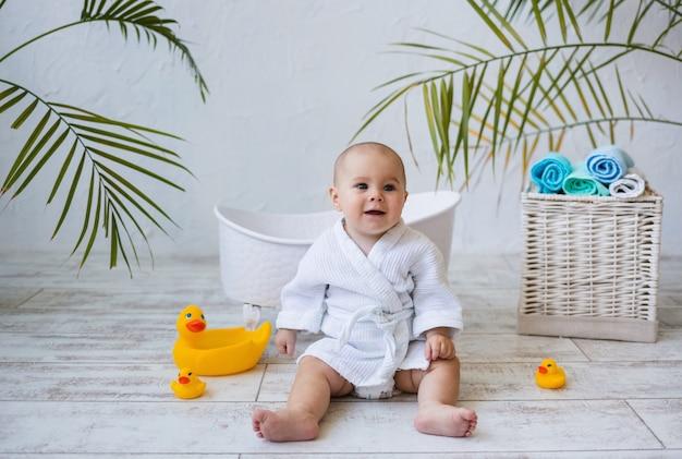 Una bambina felice in accappatoio è seduta con i giocattoli dell'anatra accanto a un bagnetto. igiene dei bambini