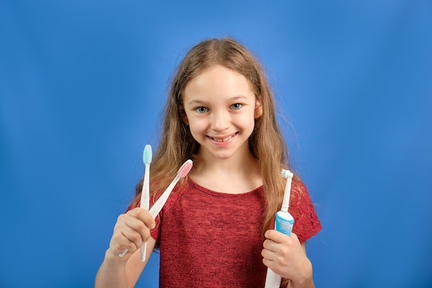 Neonata felice che pulisce i suoi denti con uno spazzolino da denti su uno spazio blu.
