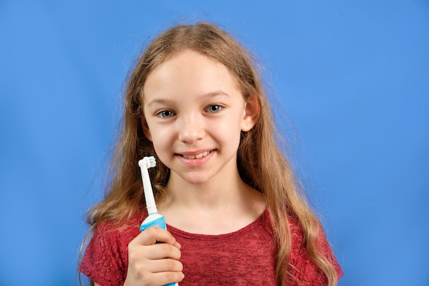 Bambina felice lavarsi i denti con uno spazzolino da denti