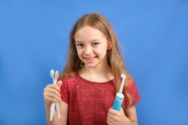 Bambina felice lavarsi i denti con spazzolini da denti
