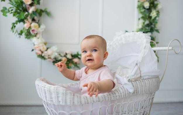 Neonata felice che si siede in un passeggino retrò su uno sfondo bianco con fiori