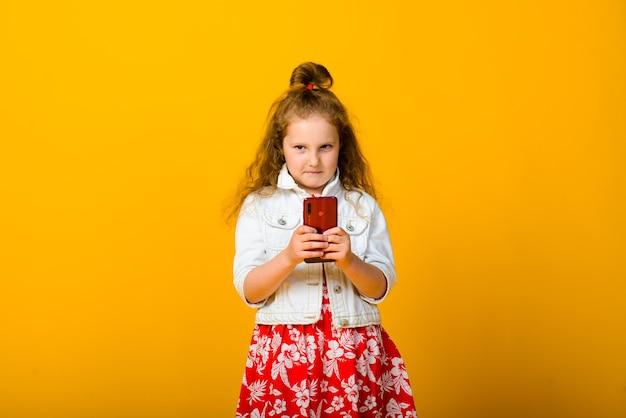 Neonata felice con il telefono isolato su giallo