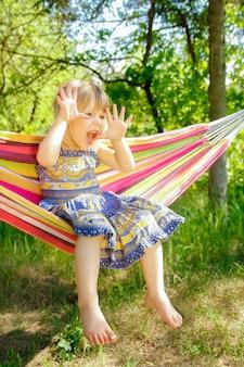 Bambino felice in un'amaca all'aperto nel parco