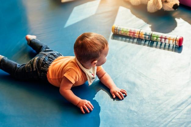 Bambino felice che gioca con i blocchi giocattolo nell'asilo.