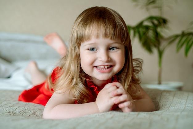 Ritratto felice del bambino neonata emozionale sul letto in una camera da letto luminosa. accogliente camera bianca, bambino allegro. grida emotivamente, ride e gioisce. coperta bianca, vestito rosso.