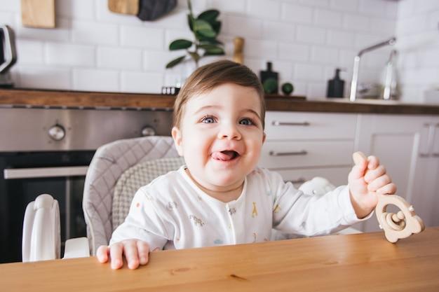 Felice bambino seduto nel seggiolone e ridendo in una moderna cucina bianca. alimentazione sana per i bambini. vista laterale del bambino sveglio
