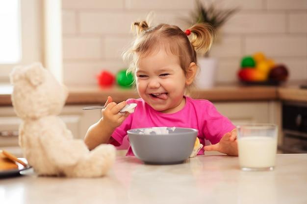 Bambino felice seduto al tavolo in cucina e mangiare con appetito