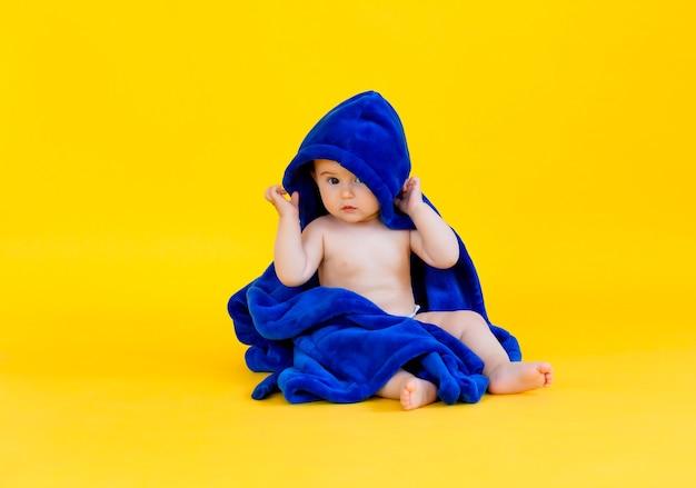 Felice baby sitter su uno sfondo giallo, avvolto in un asciugamano blu con cappuccio. bambino dopo il bagno.