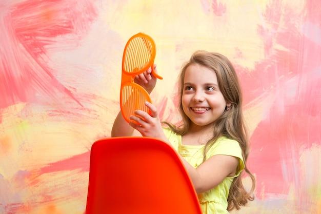 Felice bambino o piccola ragazza seduta su una sedia arancione su sfondo astratto colorato in occhiali estivi e maglietta con lunghi capelli biondi, spazio copia