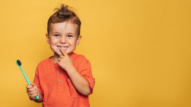 Ragazzo felice del bambino che si lava i denti con uno spazzolino da denti su uno sfondo giallo. assistenza sanitaria, igiene orale. un posto per il tuo testo.
