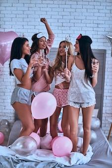 Felice di essere in giro. per tutta la lunghezza di quattro attraenti giovani donne sorridenti in pigiama che si brindano a vicenda mentre fanno un pigiama party