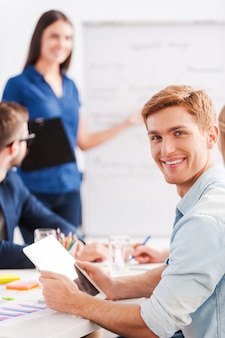 Felice di far parte di una grande squadra. fiducioso giovane in possesso di tablet digitale e sorridente mentre la donna in piedi sullo sfondo e indicando la lavagna