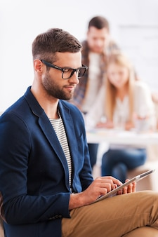 Felice di far parte della squadra. fiduciosa giovane donna in possesso di tablet digitale e sorridente mentre l'uomo in piedi sullo sfondo e indicando la lavagna