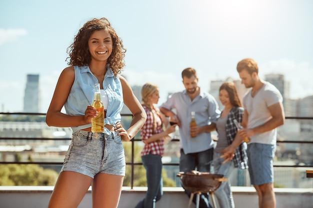 Felice di stare con gli amici, una donna giovane e allegra tiene in mano una bottiglia di birra e