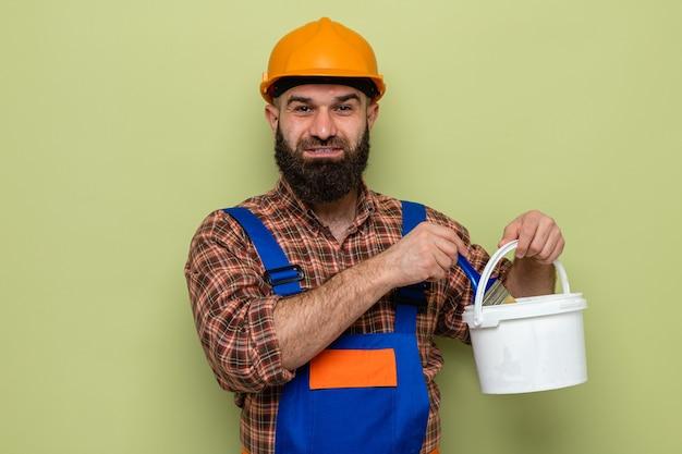 Felice uomo costruttore barbuto in uniforme da costruzione e casco di sicurezza che tiene secchio di vernice e pennello che sembra sorridente fiducioso