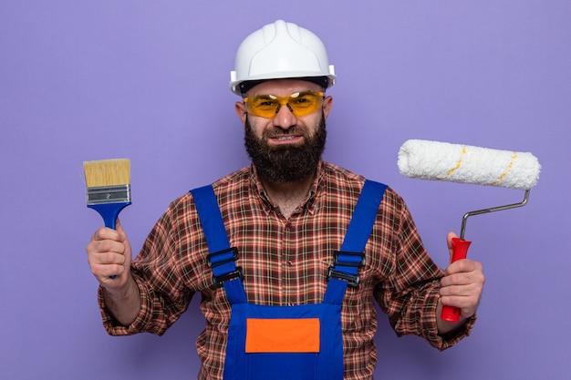 Felice costruttore barbuto in uniforme da costruzione e casco di sicurezza in occhiali di sicurezza gialli con rullo di vernice e pennello che sembrano sorridenti