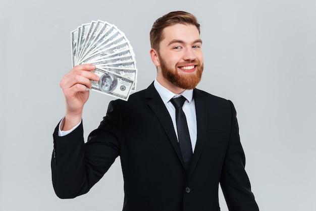 Uomo d'affari barbuto felice in abito nero che tiene i soldi in mano