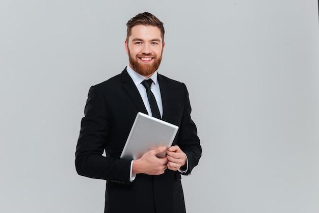 Uomo d'affari barbuto felice in abito nero che tiene in mano un computer tablet