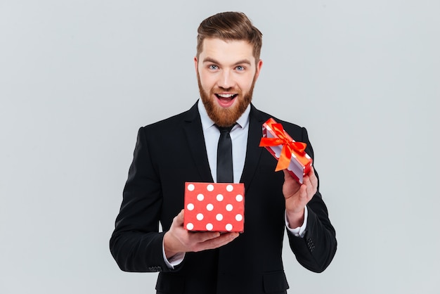 Uomo d'affari barbuto felice in regalo di apertura del vestito