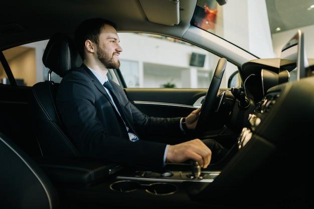 Felice uomo d'affari barbuto che indossa un tailleur è seduto al volante di una nuova auto