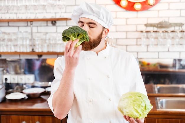 Felice chef barbuto che sente l'odore di broccoli freschi in cucina