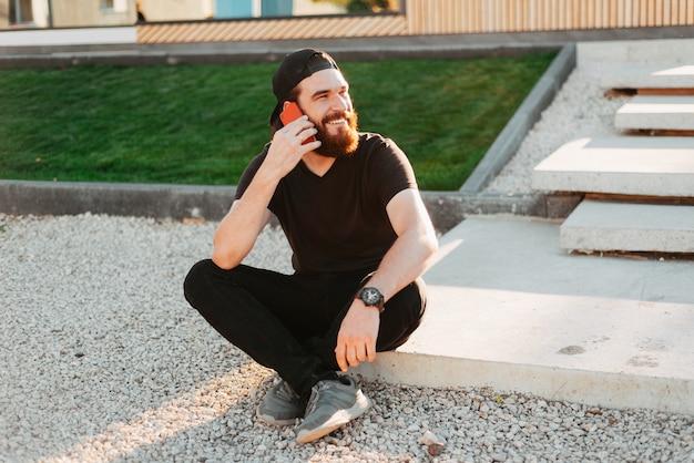 Felice hipster barbuto uomo seduto all'aperto e parlando su smartphone vicino a casa sua