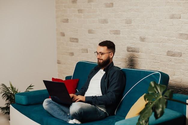 Felice maschio barbuto in occhiali poggia sul divano blu nella messaggistica di testo del soggiorno sul computer portatile.
