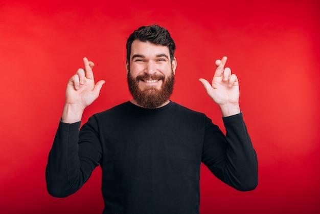 L'uomo barbuto felice che attraversa le sue dita spera in qualcosa sulla parete rossa