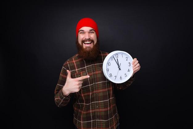 Uomo barbuto felice che tiene un orologio bianco bic e che sorride sul fondo nero.