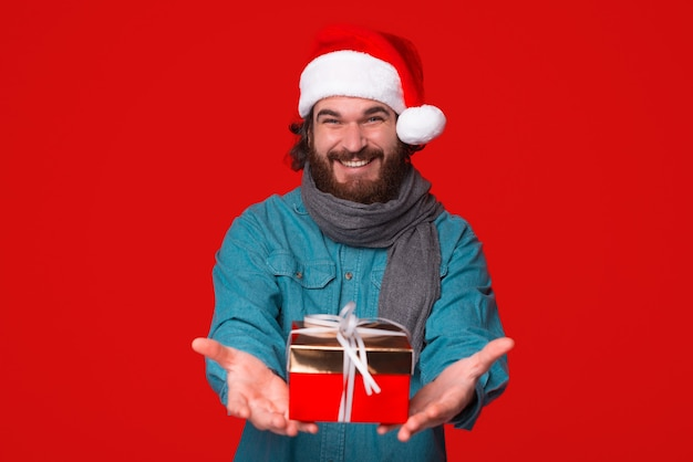 Felice l'uomo barbuto sta offrendo un regalo incartato alla fotocamera