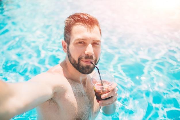 Uomo barbuto felice che fa selfie nella piscina. sta bevendo un cocktail e si sta rilassando.