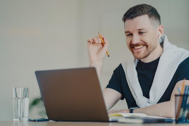 L'uomo barbuto felice prepara il lavoro del corso cartaceo lavora a distanza da casa guarda il webinar utilizza la connessione internet ad alta velocità laptop e auricolari moderni parla con il partner online. orario di lavoro.
