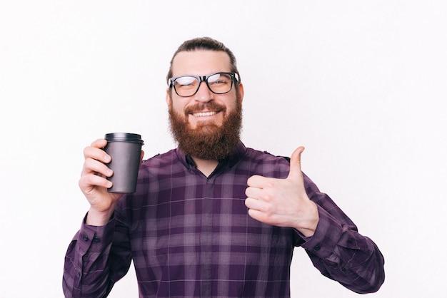 Uomo barbuto felice che mostra i pollici in su e che tiene tazza di caffè per andare