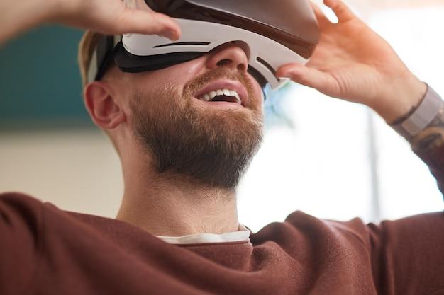 Uomo barbuto felice in cuffia per realtà virtuale