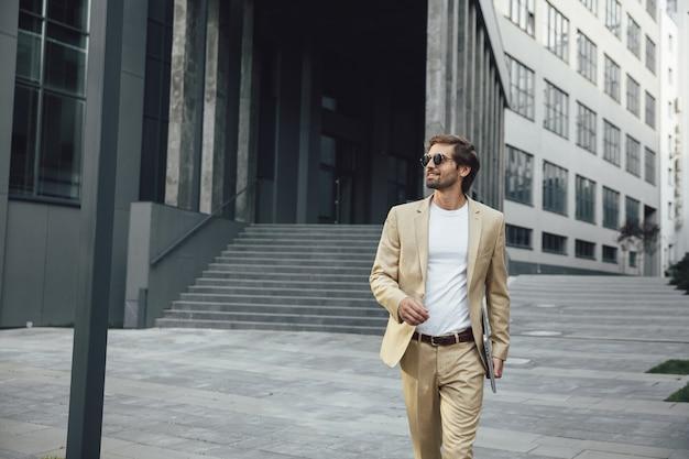 Uomo barbuto felice che cammina sulla strada con il portatile portatile in mano. fiducioso maschio indossa tailleur e occhiali da sole alla moda