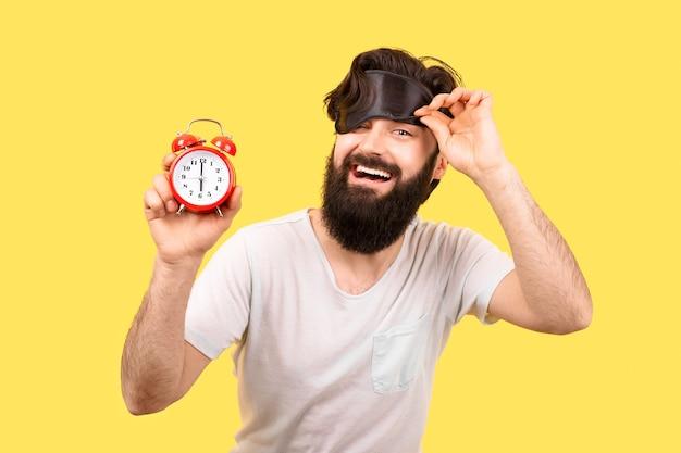 Felice uomo barbuto con maschera per dormire e sveglia su sfondo giallo, concetto buongiorno