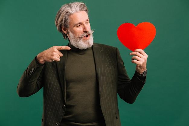 Felice uomo maturo con barba e baffi in abito color kaki con cuore rosso saluto san valentino isoleted sfondo verde.