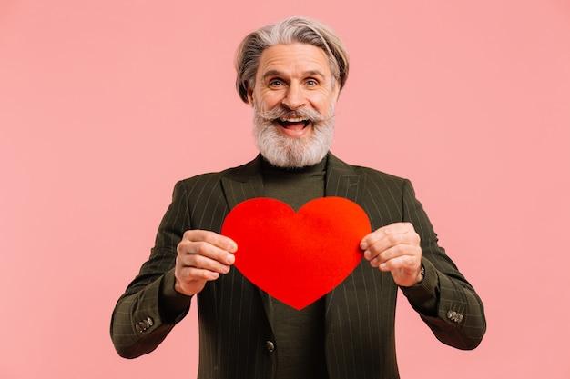 Felice uomo maturo con barba e baffi in abito color kaki con cuore rosso saluto valentine isoleted sfondo rosa.