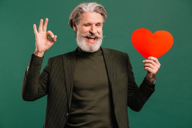 Felice uomo maturo con baffi e barba in abito cachi con cuore rosso che mostra okey saluto san valentino isoleted sfondo verde.