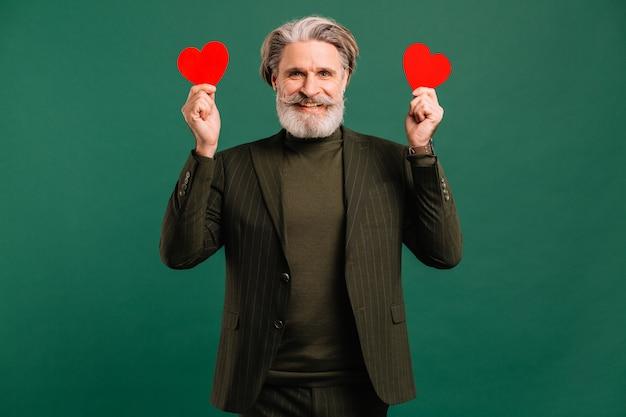 Felice uomo maturo con barba e baffi in abito color kaki con cuori rossi saluto san valentino isoleted sfondo verde.